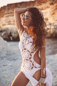 Beautiful boho styled girl wearing white crochet swimsuit with flash tattoo at the beach in sunlight poster