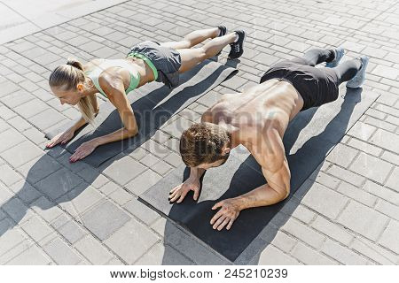 poster of Fit Fitness Woman And Man Doing Fitness Exercises Outdoor At City Background. The Best Abdominal Mus