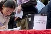 A member of the public signs a petition beside a collection bucket