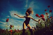 Sexy Girl With A Make. Woman Or Girl With Long Curly Hair In Black Bodysuit In Red Flower Field Of P poster