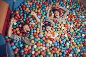 Top View. Happy Family Lying In Pool With Balls. Family Rest, Leisure Concept. Spending Holiday Toge poster