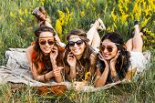 Three Cute Hippie Girl Lying On The Grass Among The Wildflowers, Best Friends Having Fun And Laughin poster