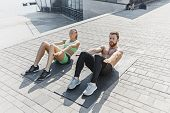 Fit Fitness Woman And Man Doing Fitness Exercises Outdoor At City Background. The Best Abdominal Mus poster