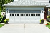 Wide Garage Door Of Residential House With Concrete Driveway In Front poster