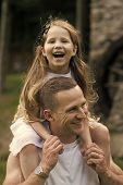 Girl On The Shoulders Of Dad. Girl Child Smile On Man Shoulders On Summer Day Outdoors. Happy Family poster