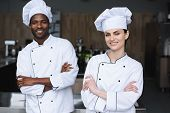 Multicultural Chefs Standing With Crossed Arms And Looking At Camera At Restaurant Kitchen poster