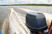 stock photo of outboard  - outboard motor boat on the river and wake - JPG