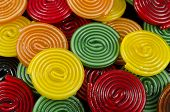 stock photo of meals wheels  - some colorful licorice candy wheels as background - JPG
