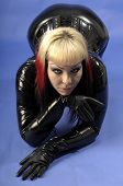image of domina  - fetish model wearing black latex against a blue background - JPG