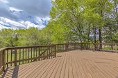 Wooden Deck With Cloudy Skies And Green Trees. Wide Angle. poster