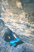 The Girl Climbs The Rock. A Woman Overcomes A Difficult Climbing Route. A Rock Climber On A Rock. Do poster
