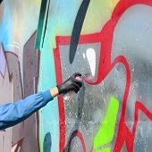 A Hand With A Spray Can That Draws A New Graffiti On The Wall. Photo Of The Process Of Drawing A Gra poster