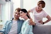 My Dear Wife. Pleasant Happy Man Hugging His Wife While Sitting With Her On The Sofa poster