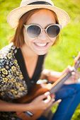 Attractive Young Woman Wearing Sunglasses And Straw Hat Playing On Brown Wooden Ukulele Outdoors. Ta poster