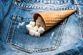 Waffle Cone With Refined Sugar On Denim Background. Cone Full Of Refined Sugar On Jeans. Diet Concep poster
