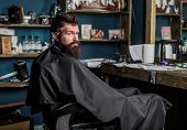 Man With Beard Covered With Black Cape Sits In Hairdressers Chair In Front Of Mirror. Man With Beard poster