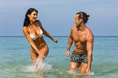 Happy Couple Laughing Together Holding Hands Running Having Fun Splashing Water In The Ocean Waves.  poster