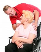 Elderly paraplegic woman sitting in a wheelchair and her male nurse.