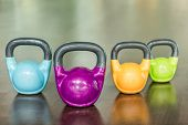 Close-up of four kettlebells of different colors and weights for intense functional training reflect poster