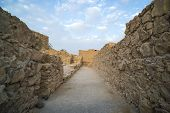 Panorama Of A Path Between Not High Ancient Stone Walls Against The Blue Cloudy Sky. Empty Way Betwe poster
