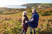 Rear View Of Loving Senior Couple Arm In Arm As They Walk Along Coast Path poster