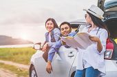 Happy Asian Woman And Her Friends Standing By Car On Coastal Road At Sunset. Young Girl Having Fun D poster