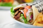 image of gyro  - beef gyro wrap with cucumber red onions and fries - JPG