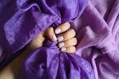 A Woman Hand With Pale Lilac Nails Holds A Purple Silk Fabric Against A Background Of Lilac Cotton F poster