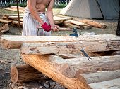 Carpenter Bare-chested In Medieval Cotton Clothes Working With Hardwood With An Ax. A Man Manually C poster
