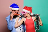Happy Man And Woman Wear Santa Hats And Funny Sunglasses. Cheerful Couple Celebrate New Year. Corpor poster