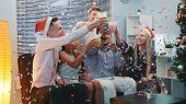 Close Up Of Cheerful Company Celebrating Christmas In Confetti Blowing While Making Cheers And Blowi poster