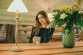 Beautiful Elegant Brunette Girl Wearing A Black Dress Is Relaxing In A Street Cafe. Advertising, Fas poster