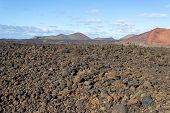 Volcanic Landscape With Lava Field In The Foreground And Mountain Range With Different Red And Brown poster