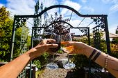 Couple Hands Toasting And Cheering Red And White Wine Glasses In The Front Of A Winery Garden Gate,  poster