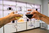 White And Red Wine Glasses Cheering Selective Focus, White Interior Design Of Modern Bottles Display poster