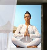 Young woman practicing yoga outdoors, sitting eyes closed in prayer position. poster