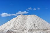 foto of salt mine  - Big pile of freshly mined salt set against a blue sky - JPG