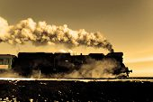 stock photo of locomotive  - Vintage steam train puffing through countryside during wintertime - JPG