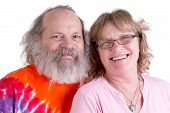 stock photo of long beard  - Happy baby boomer couple looking at you genuinly and smiling male have long beard and colorful tye dye t - JPG