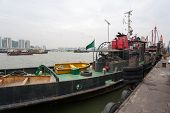 Tugboat and fishing vessels are at berth in the port of Macao. China.