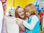 pic of outerwear  - woman and little girl choosing and trying on clothes during shopping at garment supermarket - JPG