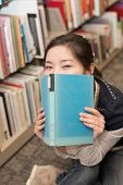 Student Covering Mouth With Book