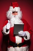 santa claus is reading about good news on his tablet pad computer, on red background