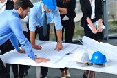 stock photo of engineering construction  - business people group on meeting and presentation  in bright modern office with construction engineer architect and worker looking building model and blueprint planbleprint plans - JPG