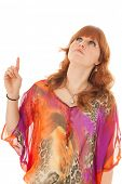 Portrait of beautiful red haired girl with colorful blouse pointing up