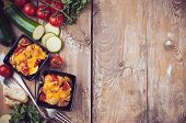 image of cherry pie  - Two dishes of vegetable casserole with cheese zucchini cherry tomatoes and oregano on a rustic wooden board with vintage cutlery food background home cooking - JPG