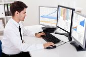 stock photo of ascending  - Over the shoulder view of the computer screens of a stock broker trading in a bull market showing ascending graphs - JPG
