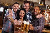 Group of happy young friends drinking beer at pub, laughing, clinking glasses