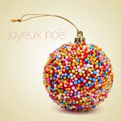 a christmas ball coated with nonpareils of different colors and the sentence joyeux noel, merry chri