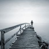 image of pier a lake  - A man on the old broken wooden pier starring at the foggy Sea - JPG